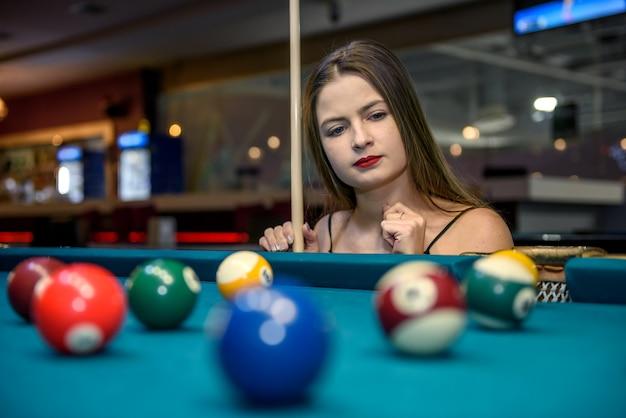 Femme avec queue posant dans un pub de billard