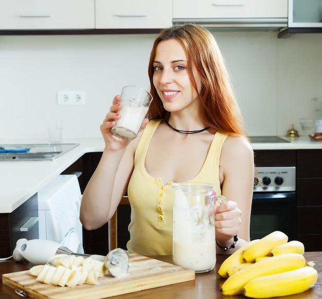 Femme qui boit le milk-shake avec des bananes