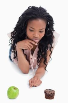 Une femme qui choisit entre une pomme ou un petit pain