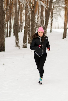 Femme qui court. coureuse de jogging dans la forêt d'hiver froid portant des vêtements de course sportifs chauds et des gants d'écouteurs. beau modèle de fitness féminin en forme.