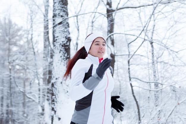 Femme qui court dans le parc d'hiver