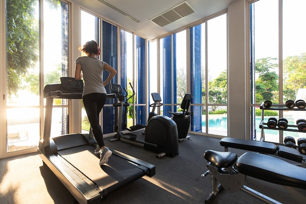 Femme qui court dans la salle de fitness sur appareils d'exercice sur tapis roulant.