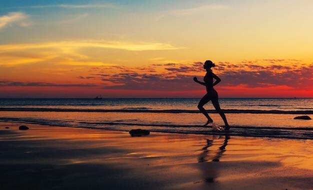 Femme qui court le long de la côte de la mer