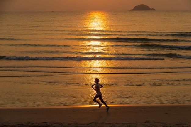 Femme qui court sur la plage au lever du soleil