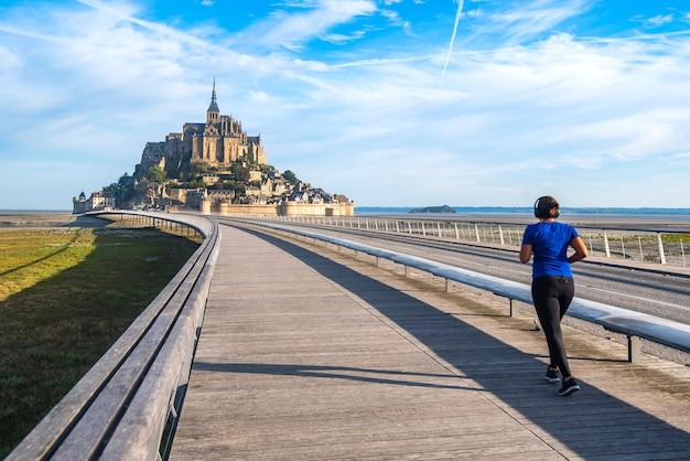 Femme qui court sur la seule route d'accès au mont saint michel. à pied est l'une des options autorisées pour l'accès.