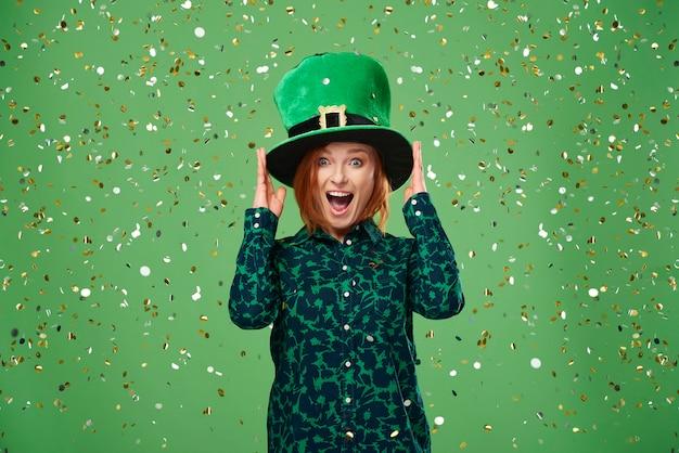 Femme qui crie avec un chapeau de lutin sous une pluie de confettis