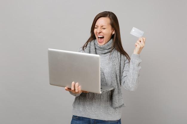 Une femme qui crie en pull, une écharpe aux yeux fermés travaille sur un ordinateur portable tenant une carte bancaire de crédit isolée sur fond gris. mode de vie sain, conseil en traitement en ligne, concept de saison froide.