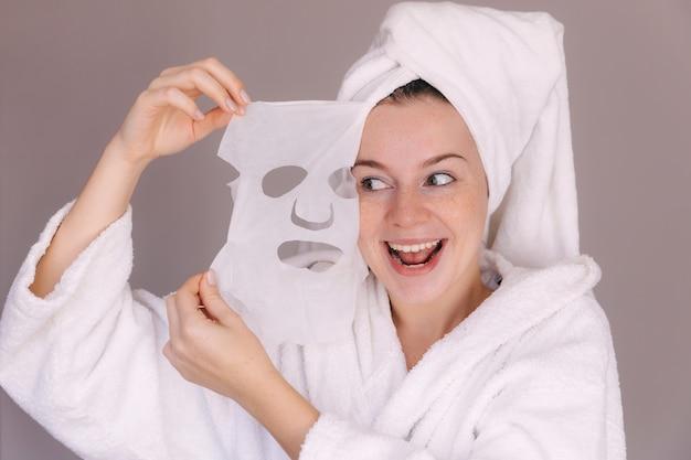 Femme qui décolle un masque cosmétique de son visage avec sourire