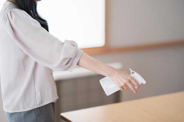 Une femme qui désinfecte et stérilise une pièce avec un spray