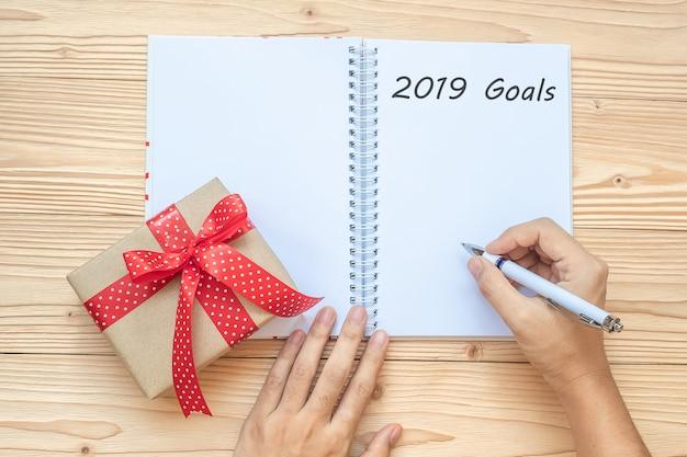Femme qui écrit les objectifs 2019 avec carnet et décoration de noël