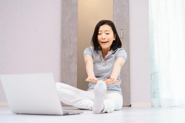 Une femme qui exerce légèrement en regardant un ordinateur et fait une expression douloureuse