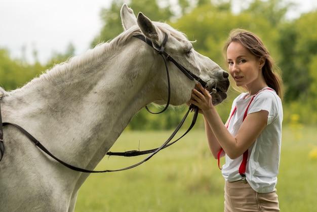 Femme qui marche avec un cheval à la campagne