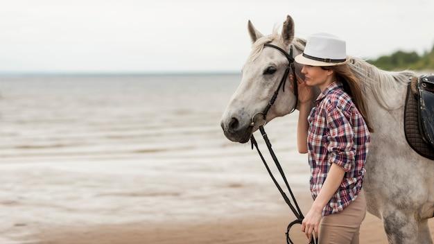 Femme qui marche avec un cheval sur la plage