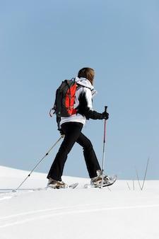 Femme qui marche dans la neige avec des raquettes