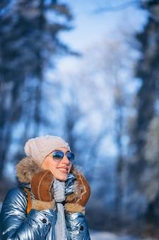 Femme qui marche dans le parc d'hiver