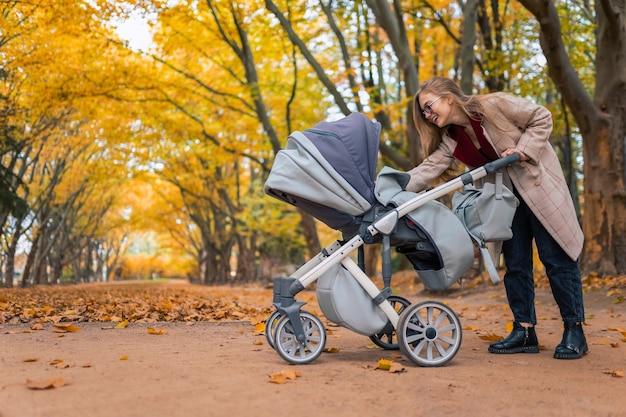 Femme qui marche dans le parc avec landau
