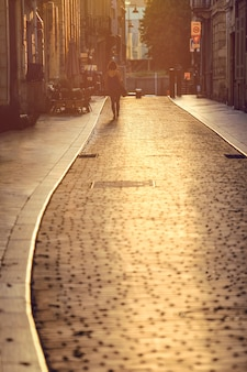Femme qui marche dans la rue au coucher du soleil à bordeaux, france