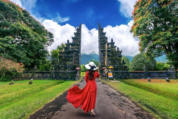 Femme qui marche à la grande porte d'entrée, bali en indonésie.