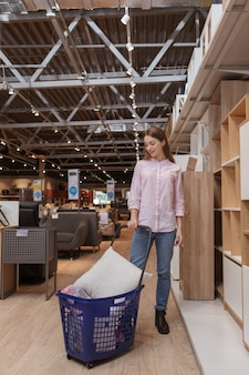 Femme qui marche avec panier au magasin de meubles