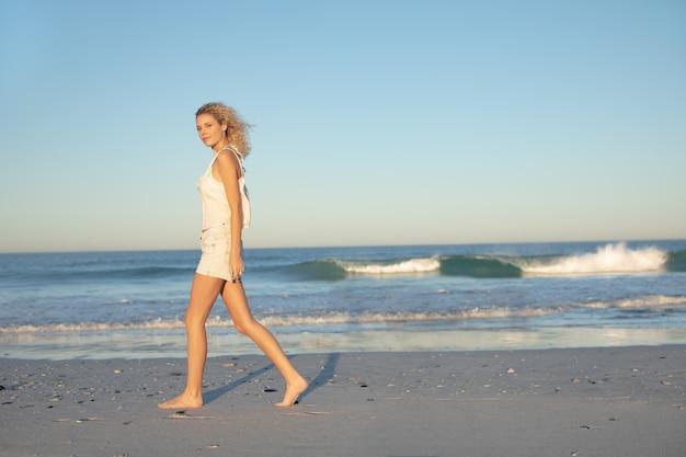 Femme qui marche pieds nus sur la plage