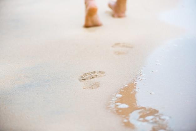 Femme qui marche sur la plage de sable laissant des traces de pas dans le sable