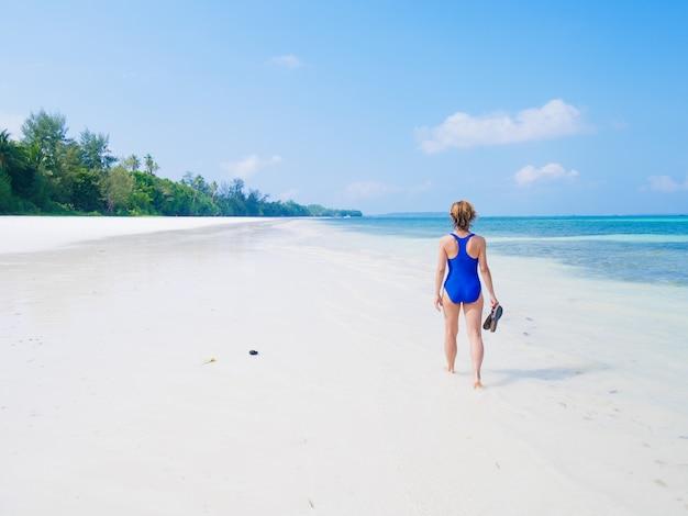 Femme qui marche sur la plage tropicale. vue arrière plage de sable blanc turquoise eau transparente mer des caraïbes de vraies personnes. indonésie kei islands moluques destination de voyage.