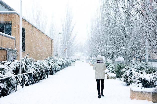 Femme qui marche sur une promenade en ville lors d'une chute de neige.