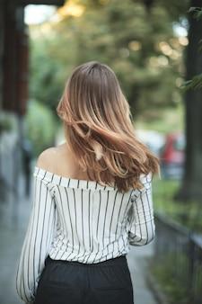 Femme qui marche avec ses beaux cheveux en mouvement