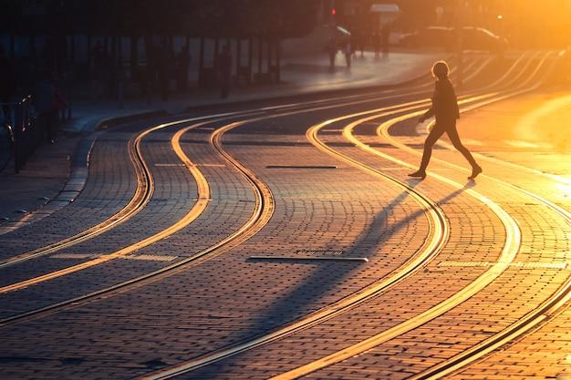 Femme qui marche sur le tramway pendant le coucher du soleil dans la ville de bordeaux, france. style vintage et texture de grain