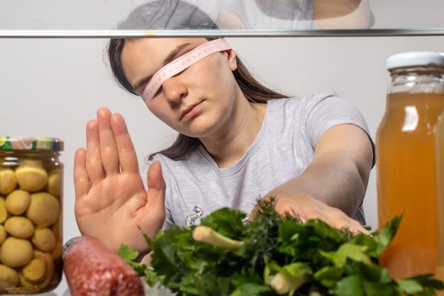 Une femme qui perd du poids refuse les saucisses à la viande et prend du persil vert et de l'oignon