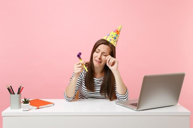 Femme qui pleure dans un chapeau de fête d'anniversaire avec jouer de la pipe célébrant seul en essuyant des larmes tout en travaillant assis au bureau blanc avec un ordinateur portable isolé sur fond rose. carrière commerciale de réussite. espace de copie.