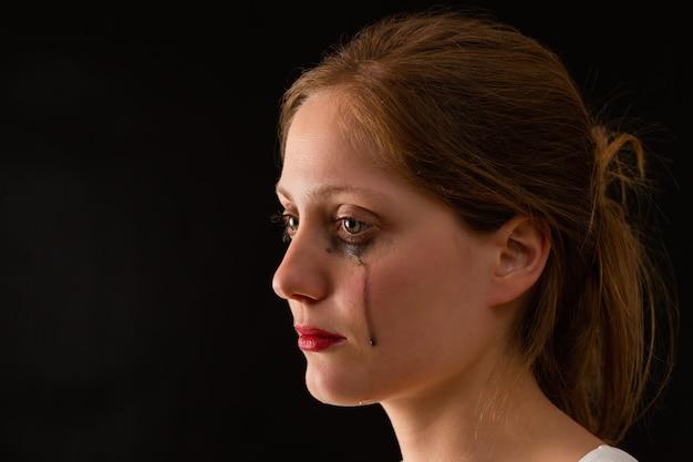 Femme qui pleure avec des larmes tombant des yeux de gros plan