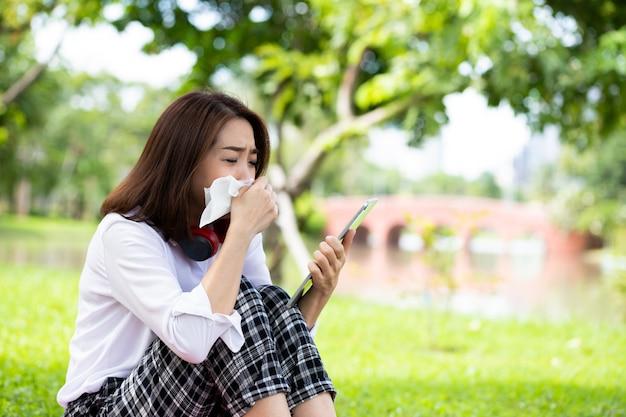 Femme qui pleure en position couchée sur l'herbe verte avec tablette à la main