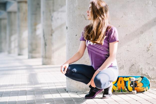 Femme qui pose avec un skateboard