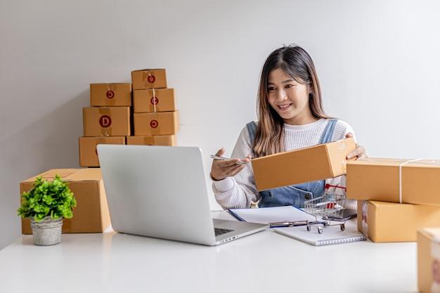 Une femme qui possède un site web de commerce électronique passe des appels vidéo en discutant avec des partenaires commerciaux et en emballant des colis, elle discute de plans marketing pour augmenter les ventes. concept de vente en ligne.