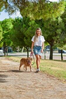 Femme qui promène le chien dans le parc.