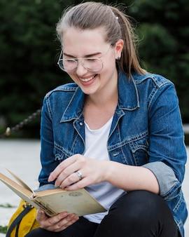 Femme qui riante avec livre assis sur la voie