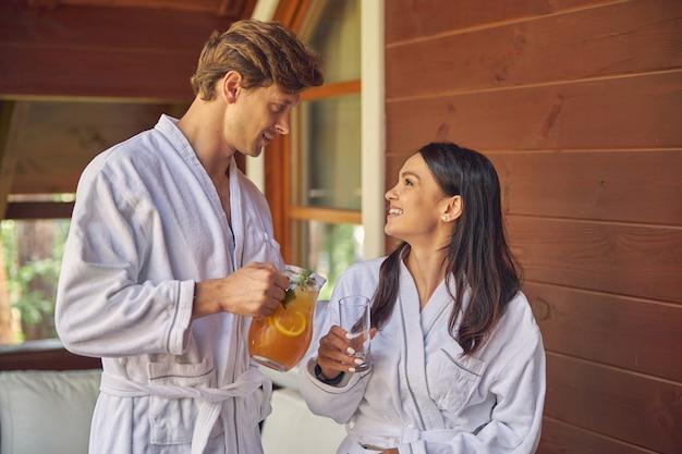 Femme qui rit et bel homme avec de la limonade orange se regardant