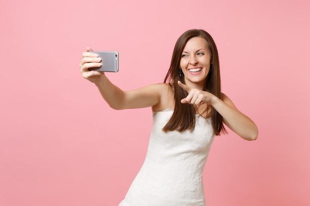 Femme qui rit en robe blanche pointant l'index sur la caméra en train de prendre une photo de selfie sur un téléphone portable, de passer un appel vidéo
