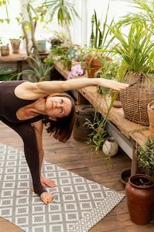 Femme qui s'étend dans la chambre avec des plantes