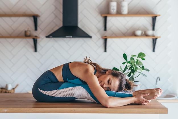 Femme Qui S'étend, Faisant Assis Se Pencher En Avant Sur Une Table. Photo Premium