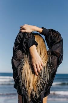 Femme qui s'étend à la plage