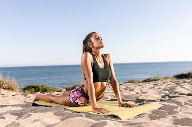 Femme qui s'étend sur le tapis de fitness
