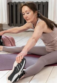 Femme qui s'étend sur un tapis de yoga