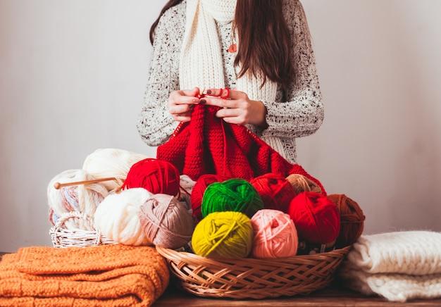 La femme qui tient des aiguilles et tricote une veste chaude rouge sur le marché