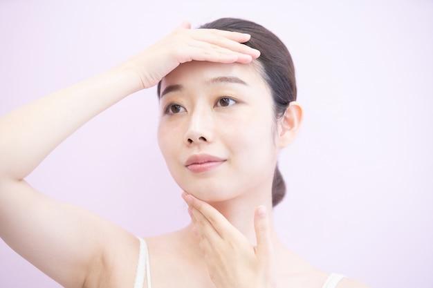 Femme qui touche et vérifie son état de peau