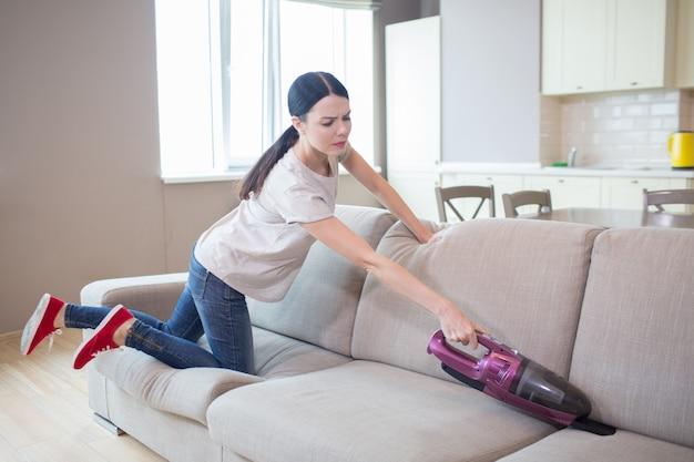 Une femme qui travaille dur se tient à genoux sur le canapé et le nettoie avec un aspirateur. elle essaie d'atteindre toutes les parties du canapé.