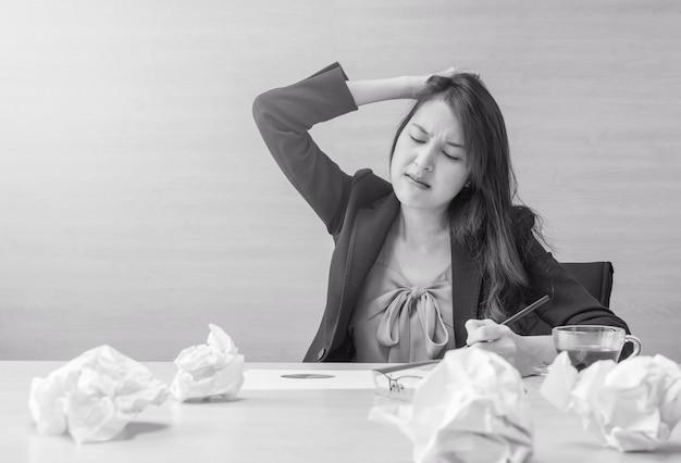 Femme qui travaille est stressée par le papier de travail devant elle dans le concept de travail