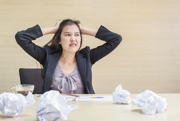 Une femme qui travaille est stressée par une pile de papier devant elle