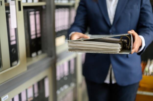 Une femme qui travaille réussit à trouver des documents de bureau